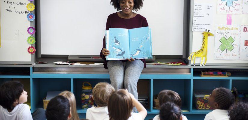 sala de aula com uma professora negra segurando um livro aberto ensinando crianças